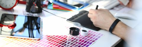 Test print paper page with colour test design fantail and magnifying glass. Lying at worktable for further promotion closeup royalty free stock images