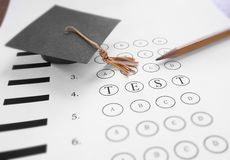 Test time. Mini mortar board graduation cap and Test text on multiple choice exam Royalty Free Stock Image