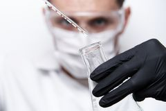 A test tube with a falling drop in a glass flask stock photography