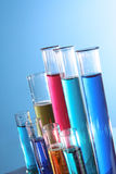 Test Tubes. Of different sizes angled on a blue background. Various colored liquids in tubes stock images