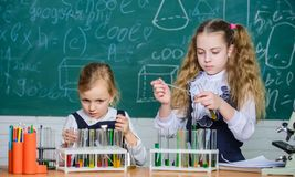 Test tubes with colorful substances. Chemical analysis and observing reaction. School equipment for laboratory. Girls on stock image