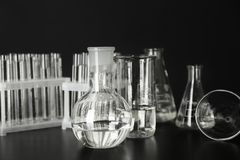 Test tubes and flasks with water on table against black background royalty free stock image