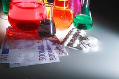 Test tubes and money. The high cost of science with test tubes and money Royalty Free Stock Photography
