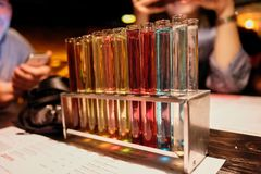 Test tubes with multi-colored liquid. Alcohol in test tubes in dark bar royalty free stock image
