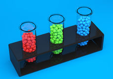 Test tubes with red, green and blue spheres. Test tube with red, green and blue spheres on blue background. 3d illustration Stock Photo