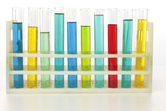 Test tubes standing in rack. Test tubes containing different colored liquids standing in a rack on a laboratory bench Stock Photos