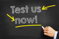 Test us now!. Hand writing with chalk Test us now! on a blackboard Stock Photography