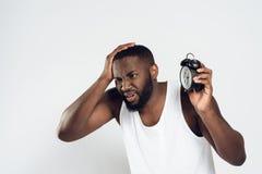 Testa afroamericana delle tenute dell'uomo con la sveglia fotografia stock