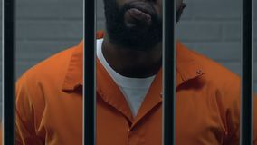 Testa afroamericana sicura della condizione della mafia in cella di prigione, criminale video d archivio