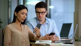 Testa arbete f?r tv? kollegor av den nya mobila appsmartphonen, programvaruteknik arkivbilder