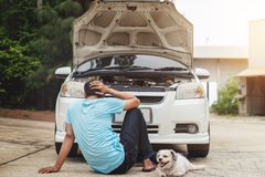 Testa asiatica sollecitata di seduta dell'uomo in mani con il cane a causa del bro Fotografie Stock