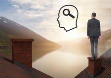 Testa con l'icona di ricerca della lente d'ingrandimento ed uomo d'affari che sta sui tetti con il camino ed il supporto del lago Fotografia Stock Libera da Diritti