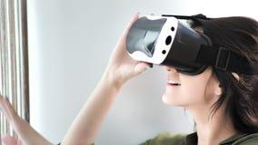 Testa del primo piano dei vetri d'uso sorridenti di realtà virtuale di ciao-tecnologia della giovane donna europea archivi video