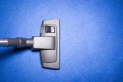 Testa dell'aspirapolvere su tappeto blu Immagine Stock