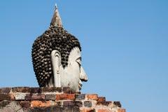 Testa di Buddha dietro la parete con chiaro cielo blu Fotografie Stock Libere da Diritti