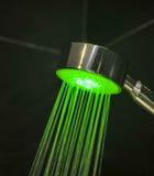 Testa di doccia colorata sul fondo nero delle mattonelle Immagine Stock