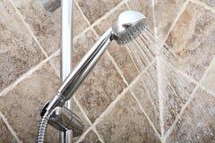 Testa di doccia con acqua corrente in un bagno Fotografia Stock