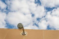 Testa di doccia sotto il cielo Immagine Stock