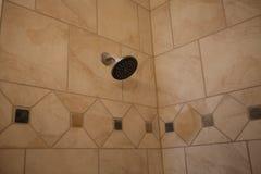 Testa di doccia sulla parete piastrellata nell'area della vasca Fotografie Stock Libere da Diritti