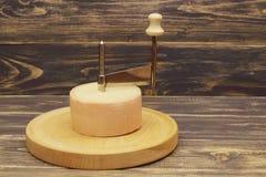 Testa di formaggio e della taglierina di formaggio saporiti invecchiati su fondo di legno scuro fotografie stock