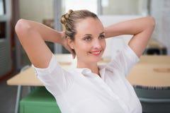 Testa di With Hands Behind della donna di affari in ufficio Immagini Stock