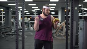 Testa di legno dell'uomo obeso ed hamburger di sollevamento giudicare disponibile, decisione di vita, motivazione archivi video