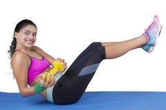 Testa di legno di sollevamento della donna e la sua gamba sulla stuoia Fotografia Stock Libera da Diritti