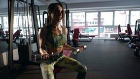 Testa di legno di sollevamento della donna, facente esercizio sul bicipite nella palestra archivi video
