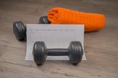 Testa di legno ed asciugamano con il piano di allenamento Fotografie Stock Libere da Diritti