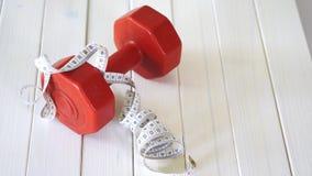 Testa di legno di forma fisica e nastro rossi di centimetro sulla tavola di legno bianca video d archivio
