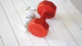Testa di legno di forma fisica e nastro rossi di centimetro sulla tavola di legno bianca archivi video