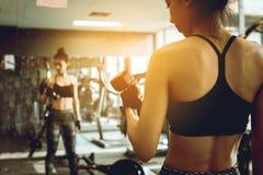 Testa di legno di sollevamento della donna asiatica davanti allo specchio nella palestra di forma fisica Fotografia Stock Libera da Diritti