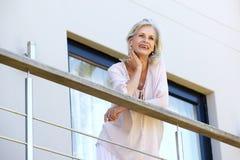 Testa di riposo attraente della donna più anziana a disposizione che sta sul terrazzo Fotografia Stock Libera da Diritti