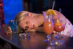Testa di riposo ubriaca della giovane donna sul contatore della barra Fotografia Stock