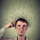 Testa di scratch dell'uomo, pensante con il cervello che si fonde in molte linee punti interrogativi Immagini Stock