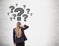 Testa di scratch della donna e punti interrogativi sul muro di cemento Immagini Stock