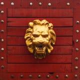 Testa dorata del leone su legno rosso Immagine Stock Libera da Diritti