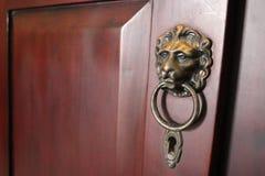 Testa e buco della serratura dorati del leone della maniglia della porta fotografie stock