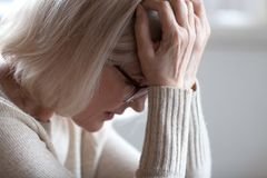 Testa senior stanca triste della tenuta della donna in mani che ritengono emicrania immagini stock