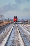 Testa sulla vista del treno rosso distante con l'orizzonte della città Immagine Stock