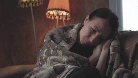 Testa triste depressa della tenuta della donna in mani che si siedono sulla poltrona a casa Ritratto drammatico di stile di vita  video d archivio