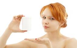 Testarossa adorabile che mostra il contenitore in bianco del farmaco Fotografie Stock