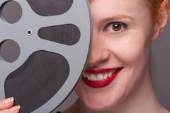 Testarossa attraente con la bobina di film fotografia stock libera da diritti