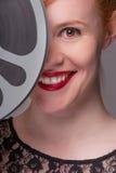 Testarossa attraente con la bobina di film immagini stock libere da diritti