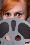 Testarossa attraente sorridente che esamina la bobina di film immagini stock