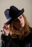 Testarossa in black hat con la testa inclinata Immagine Stock