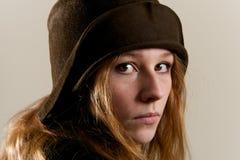 Testarossa in cappello marrone della campana di vetro che sembra serio Fotografie Stock Libere da Diritti