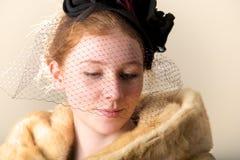 Testarossa in cappello nero e pelliccia velati che guardano giù Immagine Stock Libera da Diritti