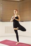 Testarossa che equilibra su una posa di yoga della gamba Fotografie Stock