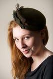 Testarossa che sorride insolente in cappello messo le piume a verde Fotografia Stock Libera da Diritti